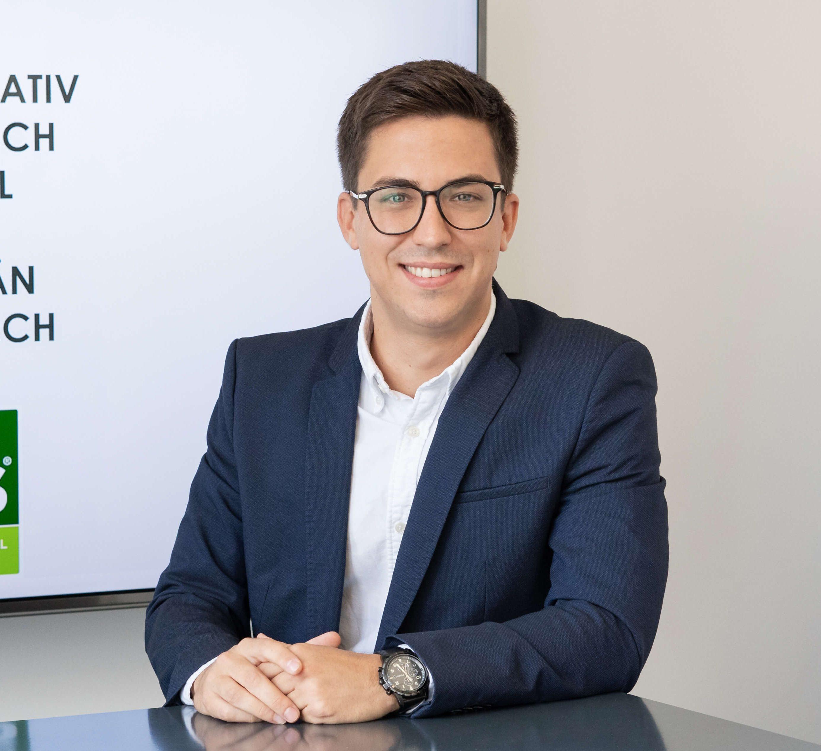 Ein junger Mann in Anzug lächelt in die Kamera, im Hintergrund das Logo von TMS Trademarketing Service GmbH