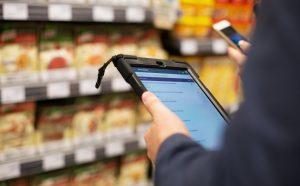 Blick auf Tablet vor Supermarktregal