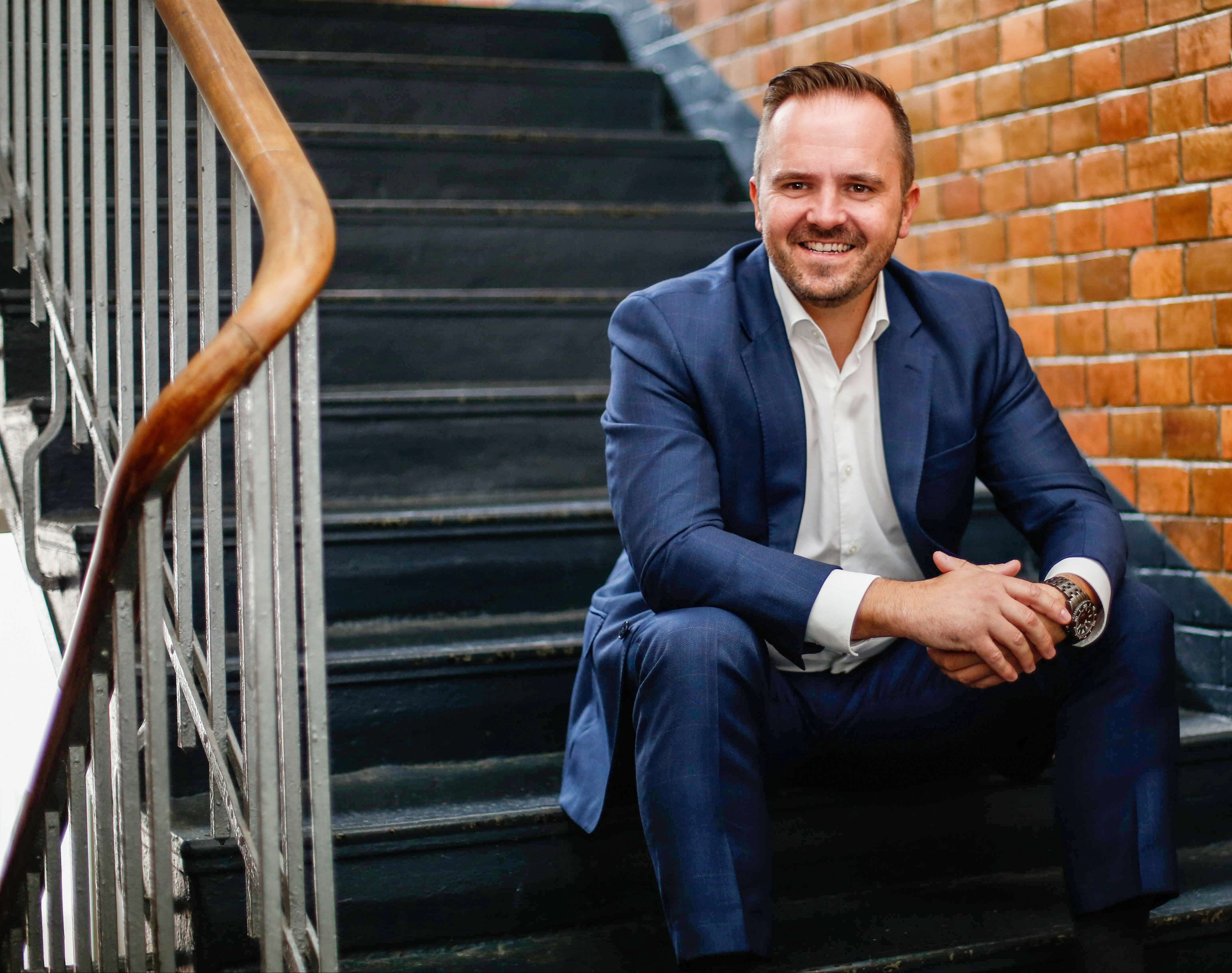 Hrvoje Klobucar, Director of Permanent Placement, sitzt auf einer Treppe und lächelt