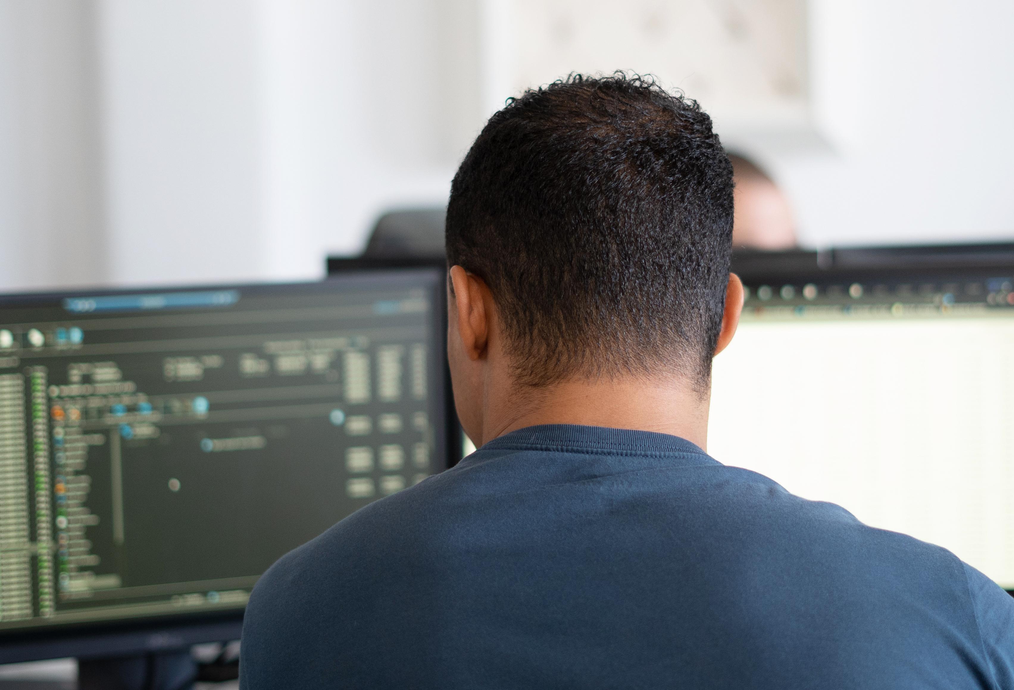 Entwickler von hinten bei der Arbeit am PC