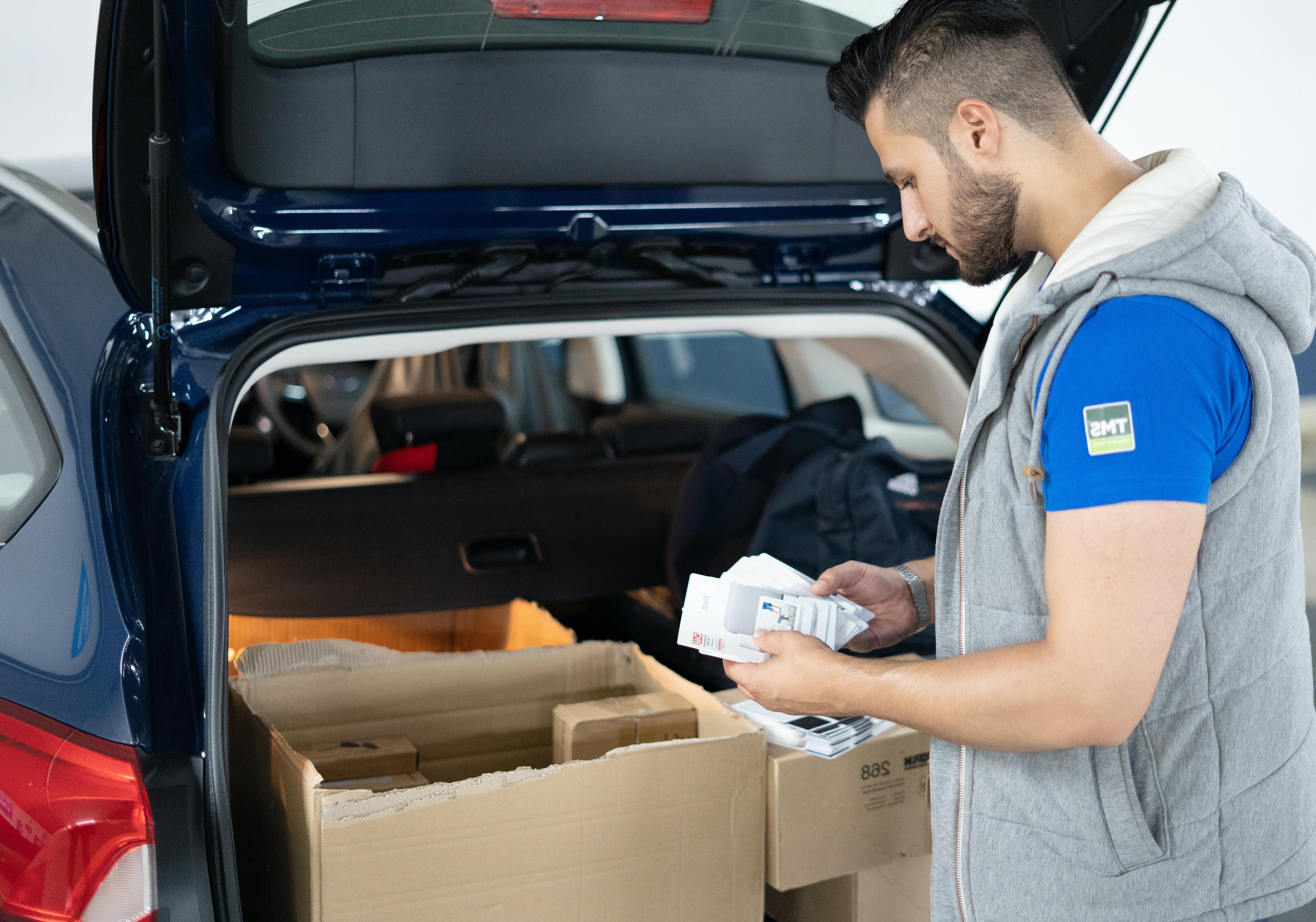 Kontrolle von Werbematerialien vor der Aktion im Kofferraum des Firmenwagens
