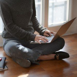 Frau vor Fenster mit Laptop auf dem Schoß