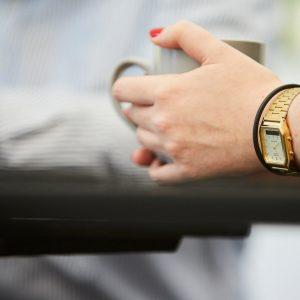 Frauenhand mit Golduhr und Armband eine Tasse umfassend