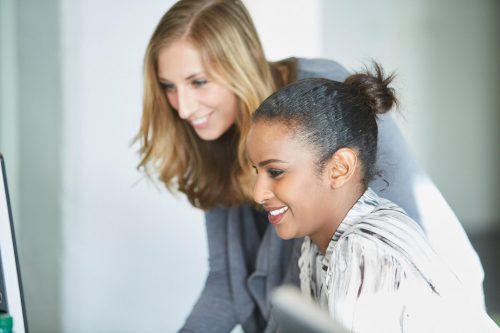 Zwei junge TMS Mitarbeiterinnen, die lächeln
