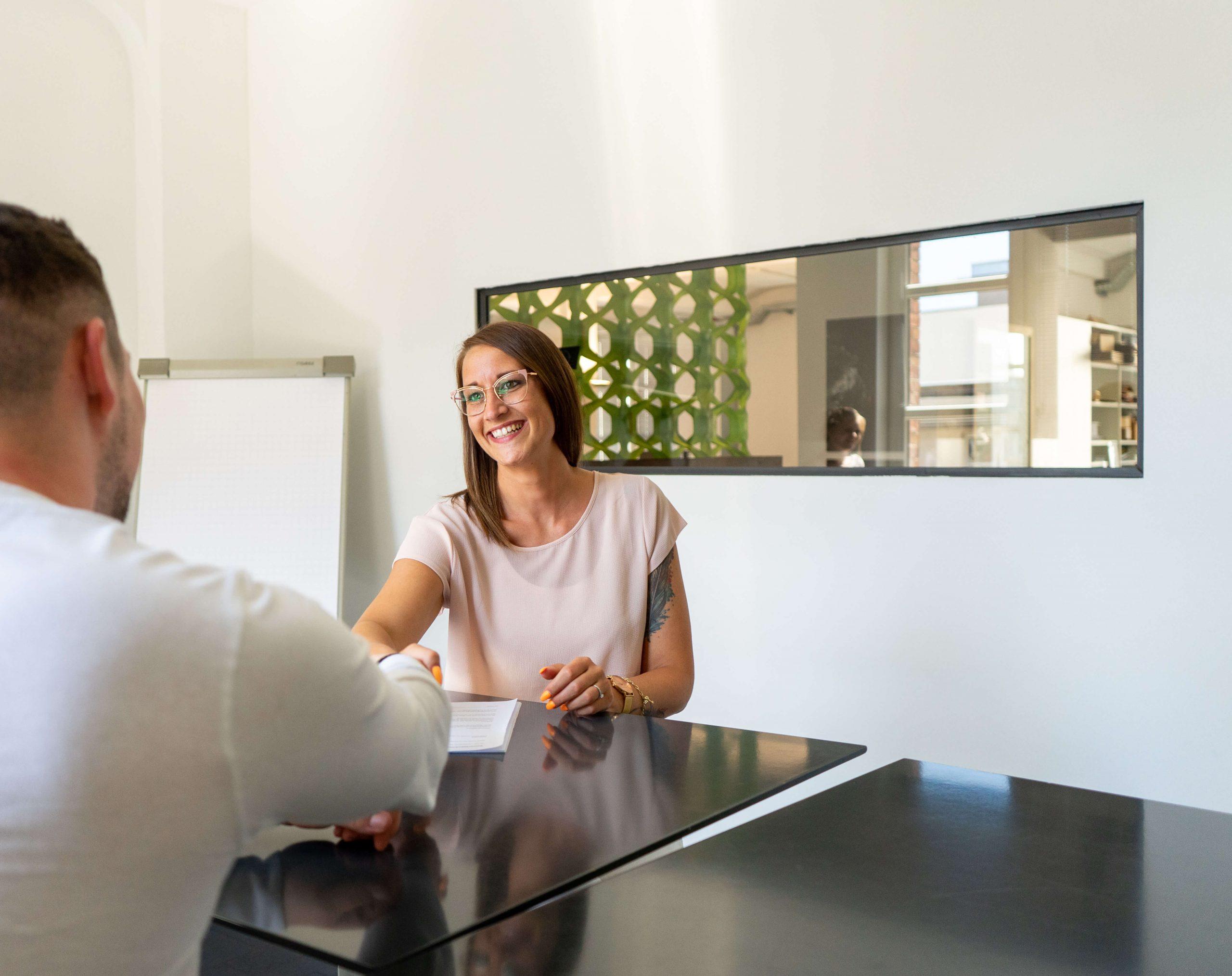 Eine Personalerin spricht mit einem Merchandiser und schüttelt seine Hand