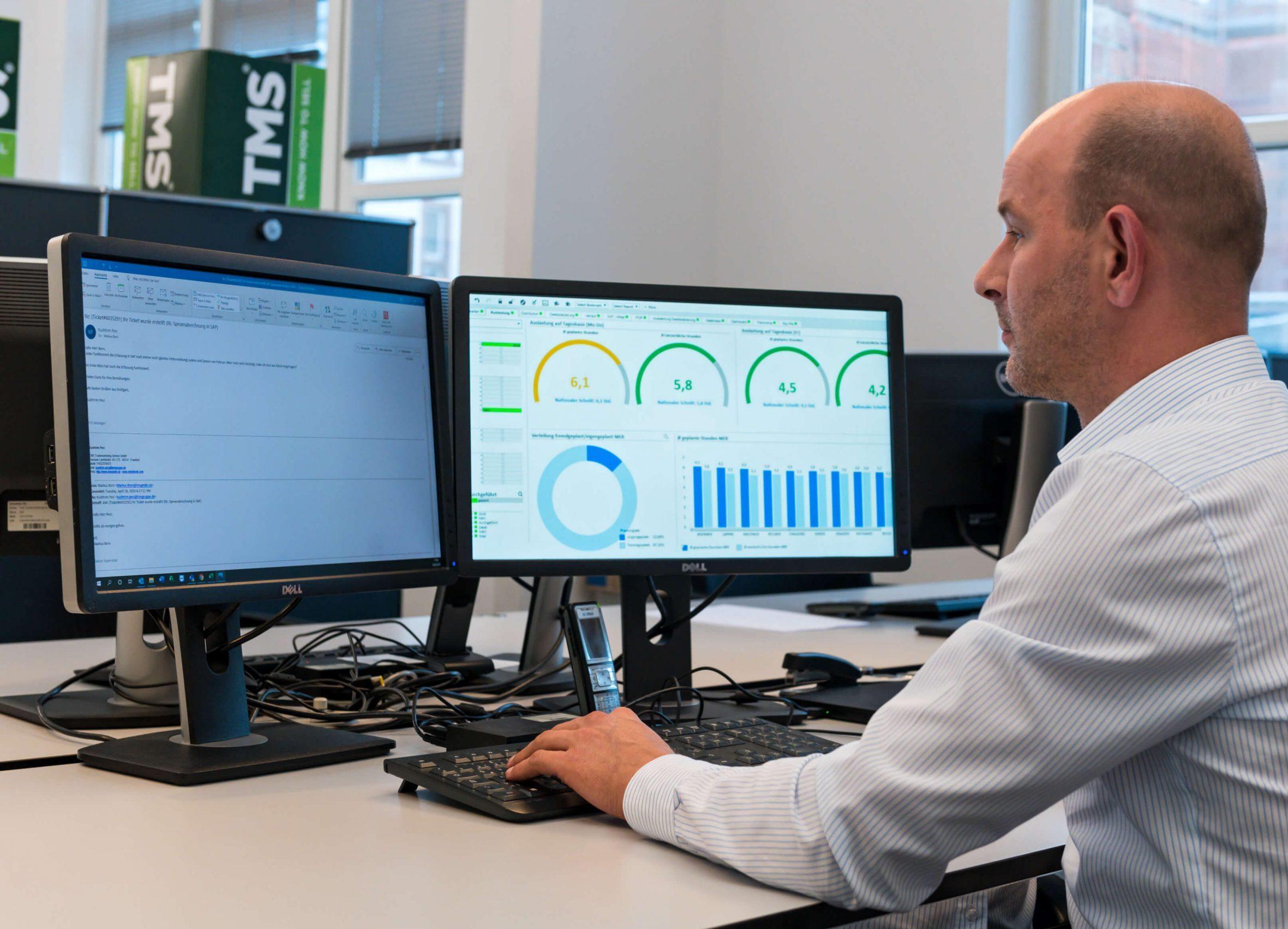 Ein Mann sitzt vor einem Bildschirm mit Auswertungen