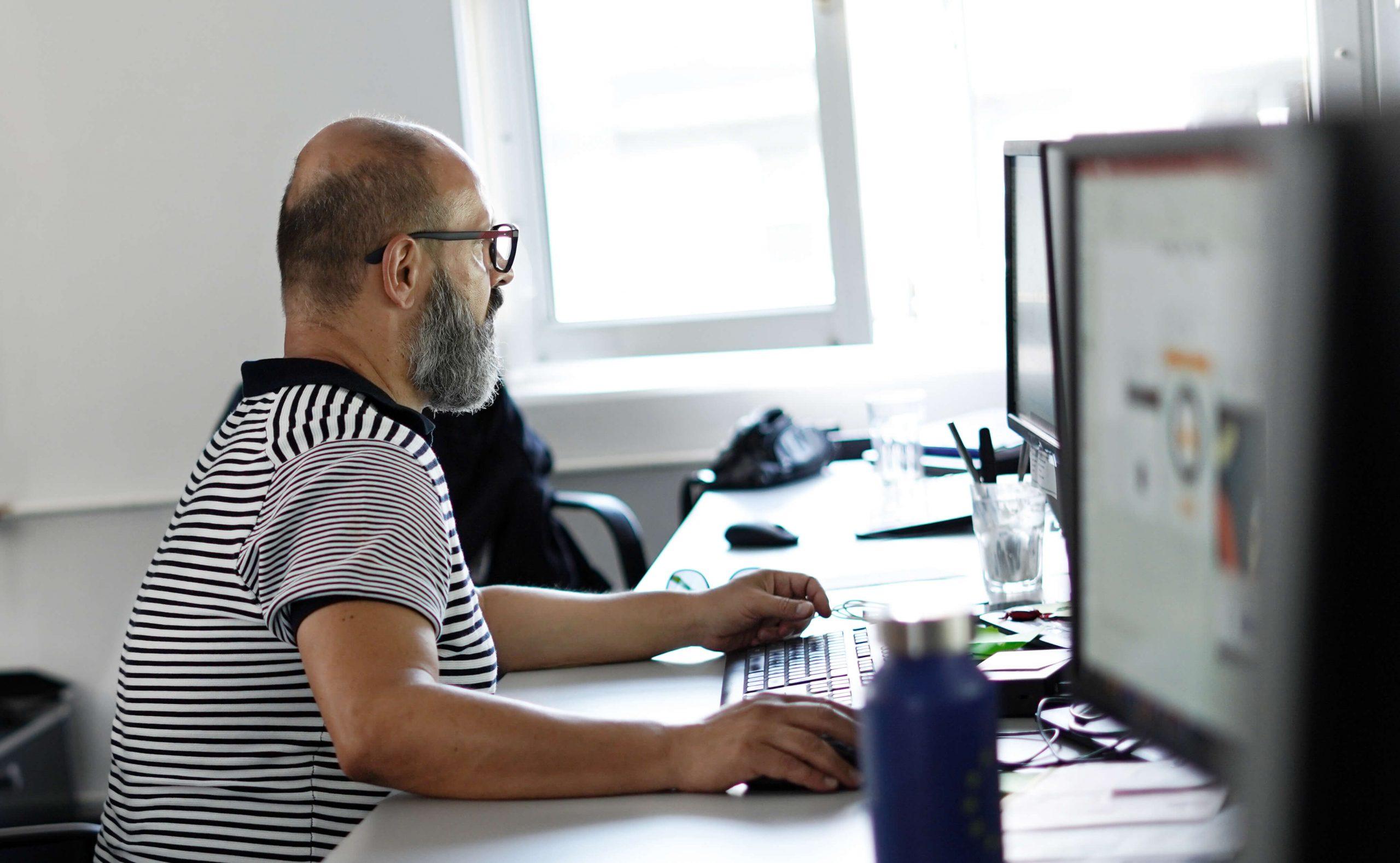 Ein Mann sitzt am Schreibtisch und fertigt ein Reporting an