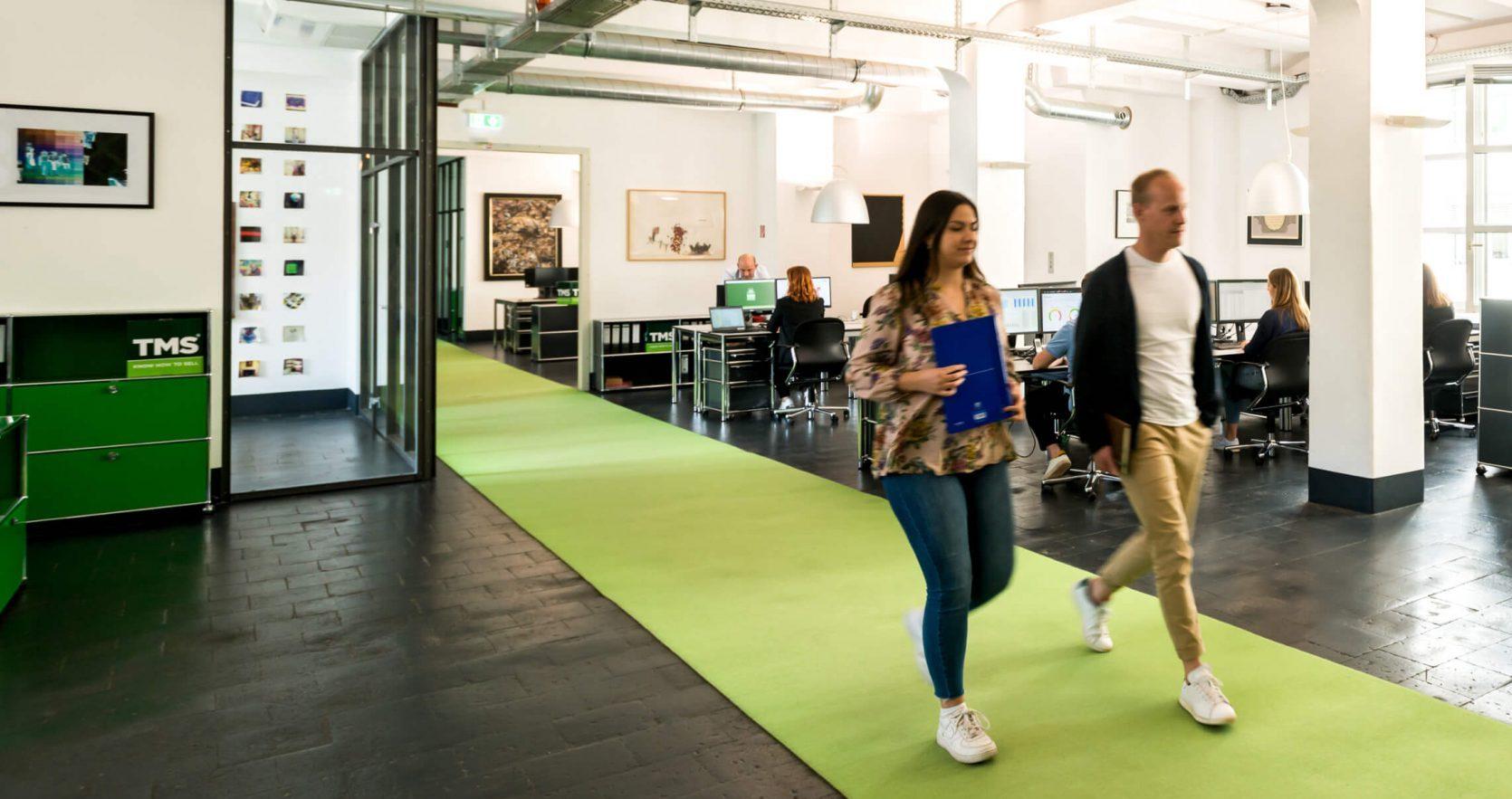 Zwei Mitarbeiter der TMS laufen durch das Büro
