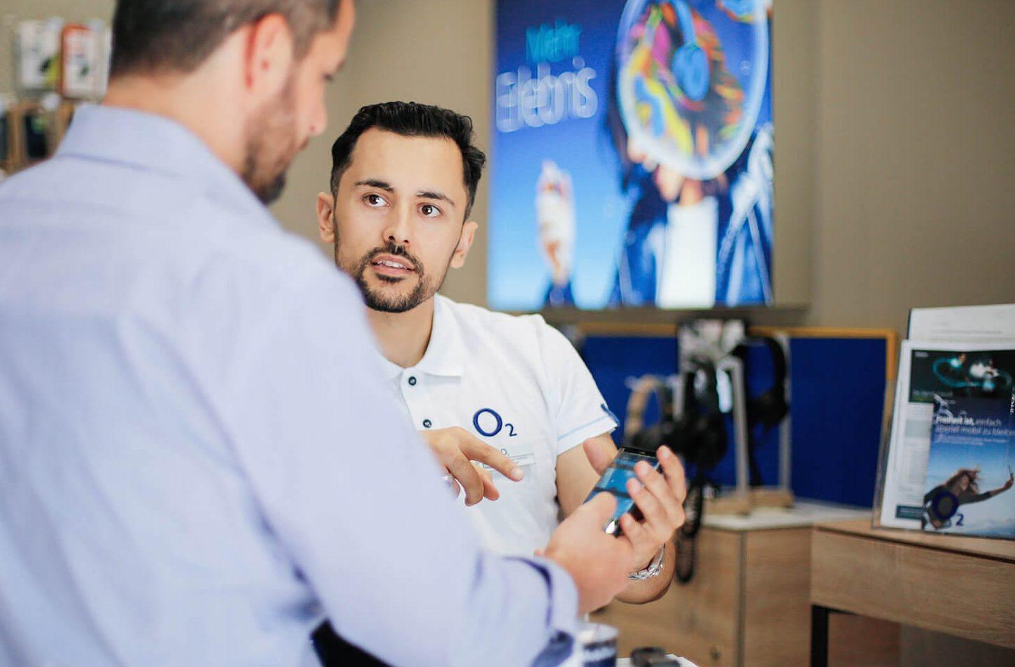 Zwei Männer stehen zusammen. Einer demonstriert ein Smartphone in einem Verkaufsgespräch