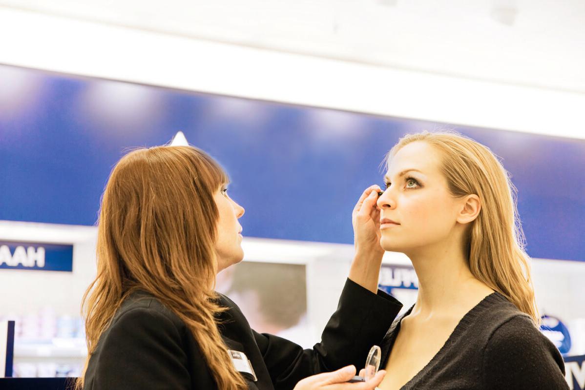 Eine blonde Frau wird von einer Sales Promoterin geschminkt