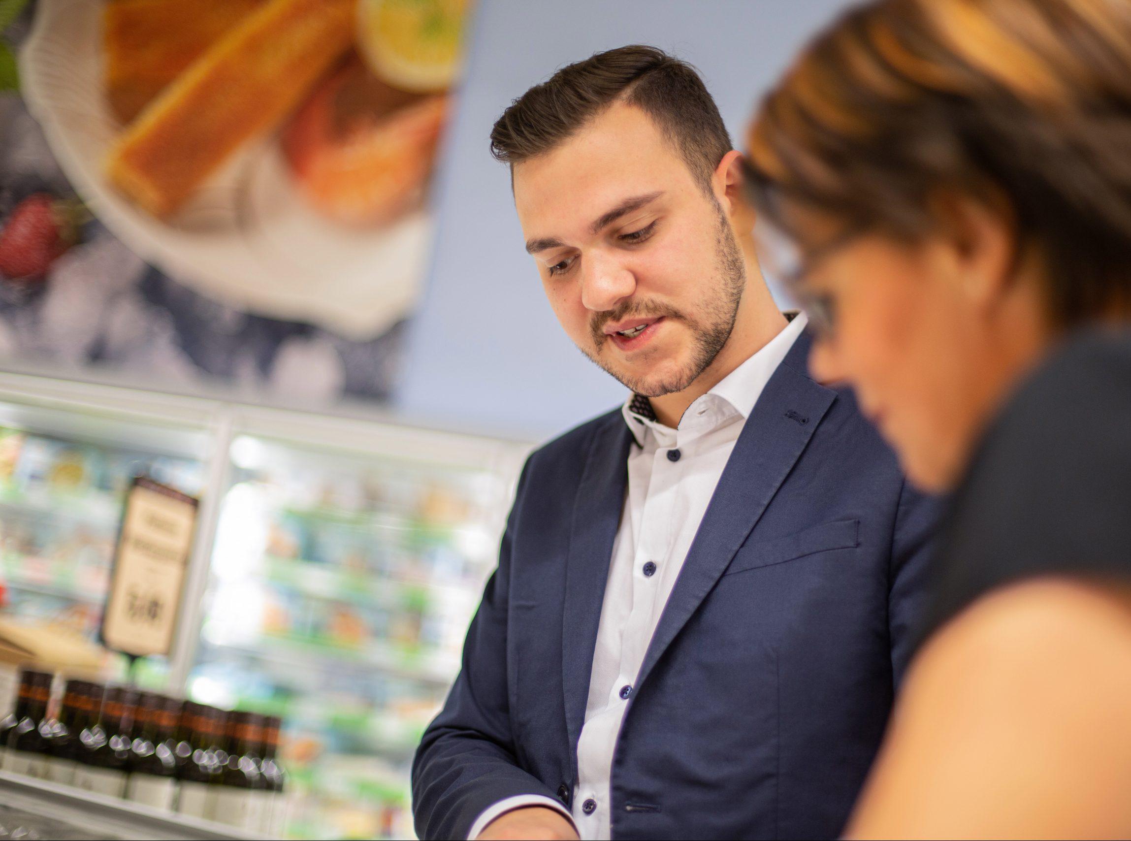 Ein Sales Promoter spricht lächelnd mit einer anderen Person
