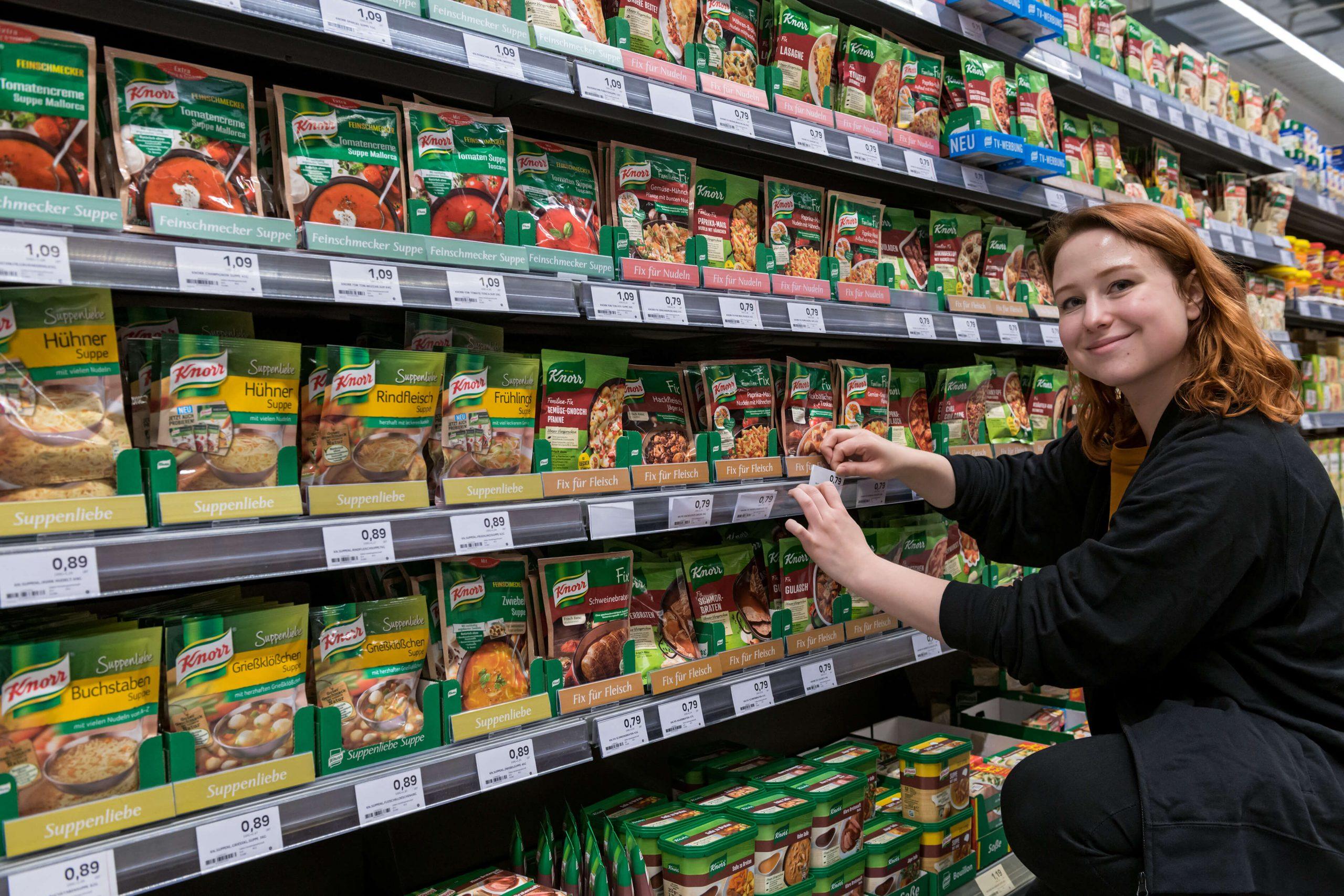 Eine junge Frau verräumt Waren und führt Shelf Management für TMS durch