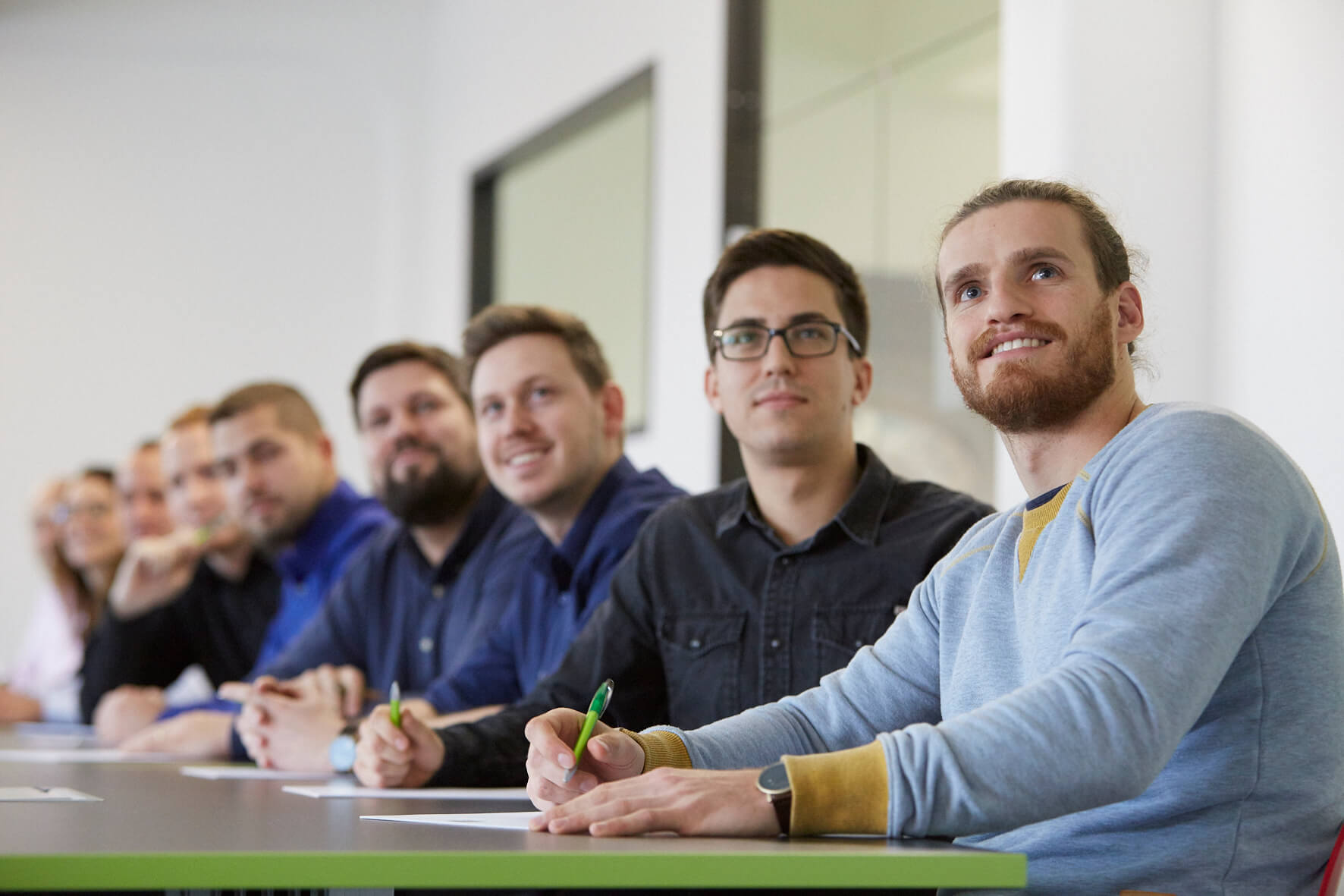Eine Personengruppe hört einem Trainer bei einer Informationstagung zu