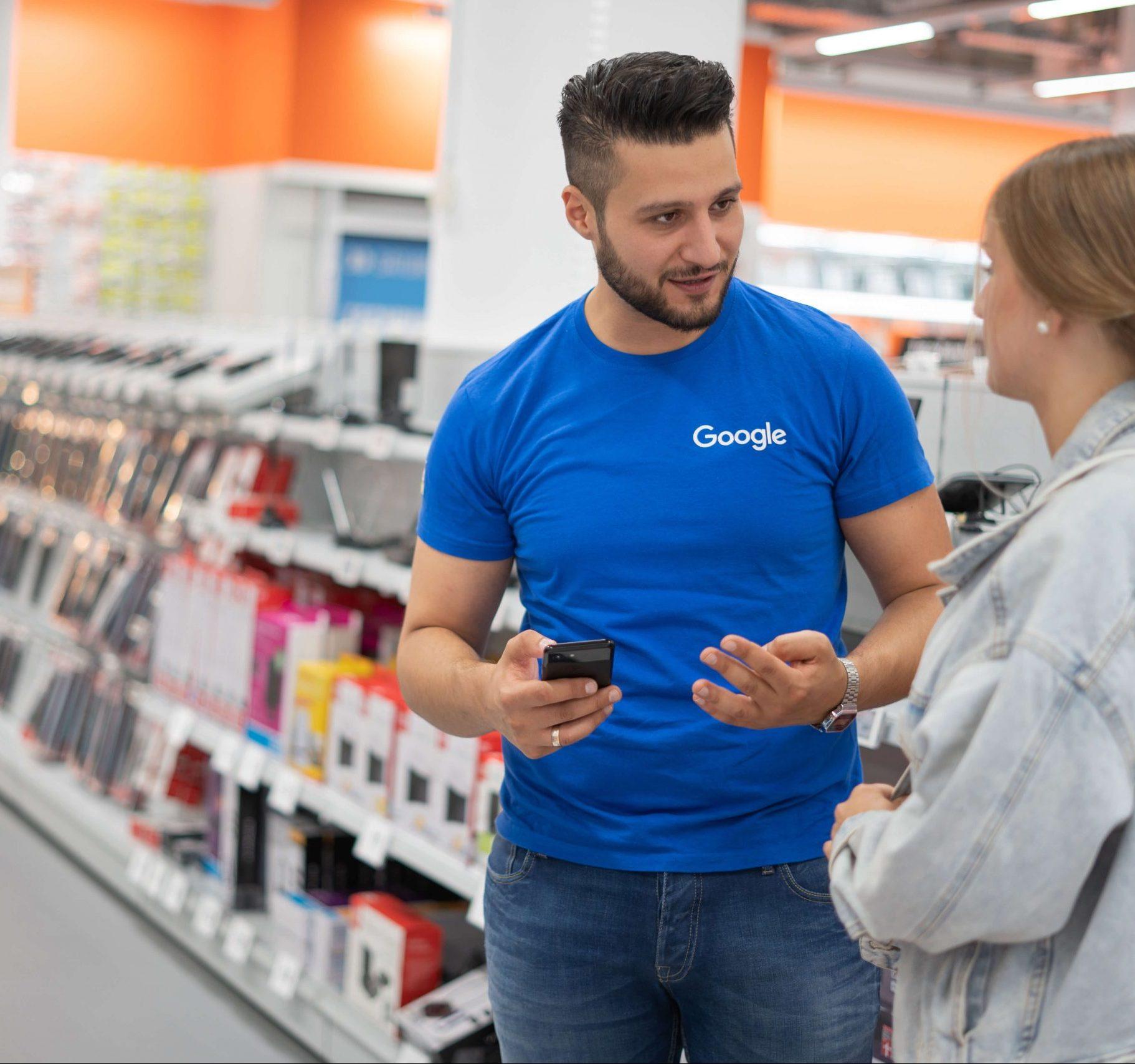 Ein Mitarbeiter von TMS steht in einem Saturn-Markt und spricht mit einem Kunden