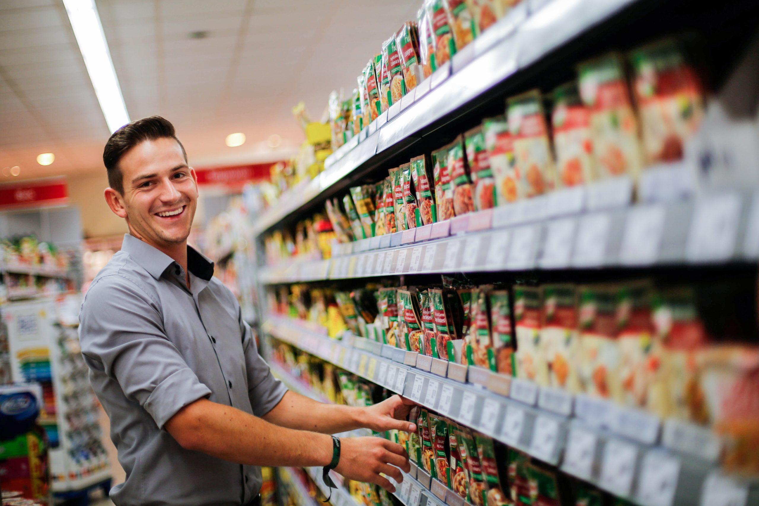 Ein Mitarbeiter steht am Regal zur Warendisposition und lächelt