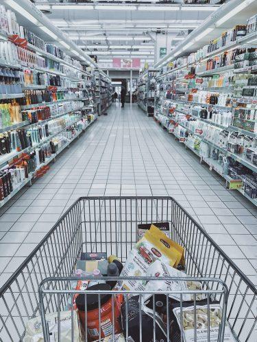 Ein gefüllter Einkaufswegen in einer Regalreihe im Supermarkt