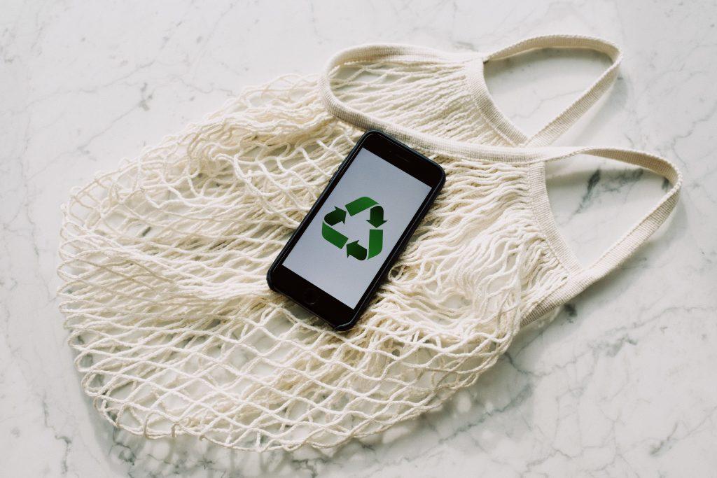 Eine wieder verwendbare, nachhaltige Einkaufstasche und ein Smartphone mit dem Recycling-Symbol symbolisieren den Retail Trend Nachhaltigkeit.