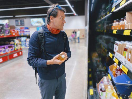 Ein Shopper betrachtet Produkte in einem Regal am Point of Sale