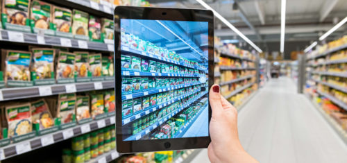 Ein Außendienstmitarbeiter hält ein Tablet hoch und erfasst Smart Data am Point of Sale